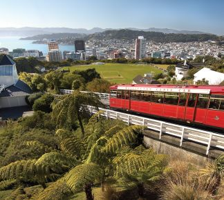 A Train On A Steel Track With Wellington Cable Car In The Background